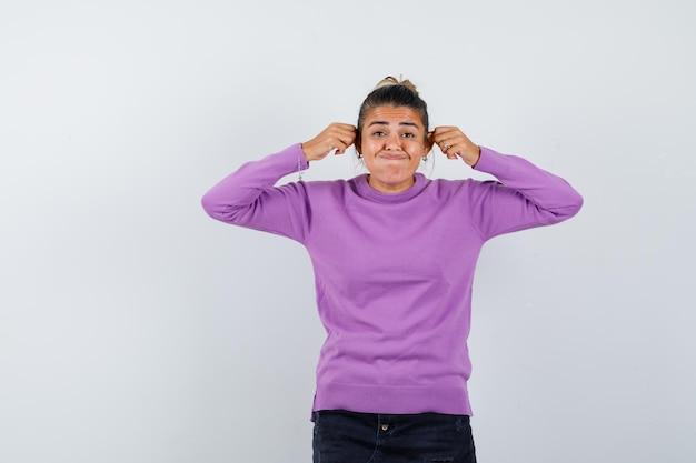 Vrouw in wollen blouse die haar oren naar beneden trekt en er grappig uitziet