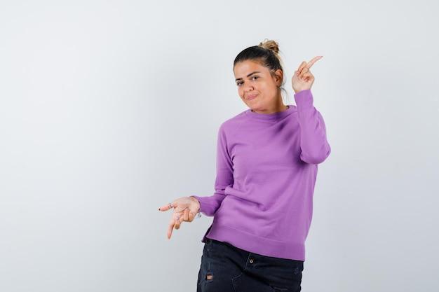 Vrouw in wollen blouse die met de vingers op en neer wijst en er zelfverzekerd uitziet