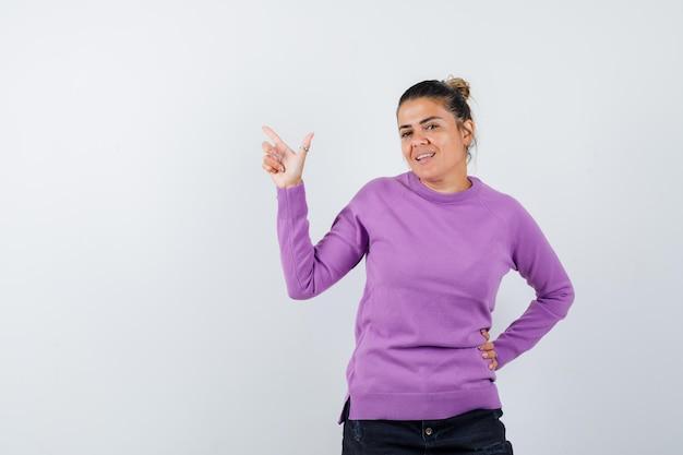 Vrouw in wollen blouse die naar boven wijst en er zelfverzekerd uitziet