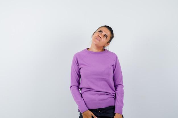 Vrouw in wollen blouse kijkt op en kijkt aarzelend