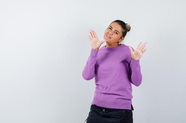 Vrouw in wollen blouse zwaait met de handen om afscheid te nemen en ziet er vrolijk uit