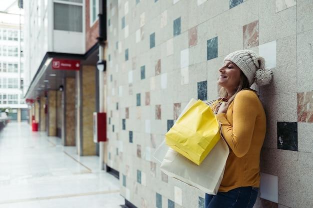 Vrouw in wollen hoed lachend met boodschappentassen.