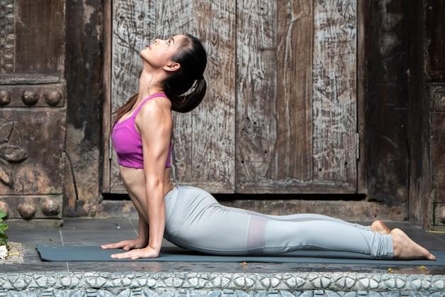 Vrouw in yoga-oefeningen aanhef aan zon surya namaskar.
