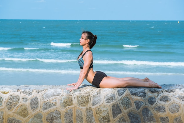 Vrouw in yoga pose op strand, yoga retraite en training.