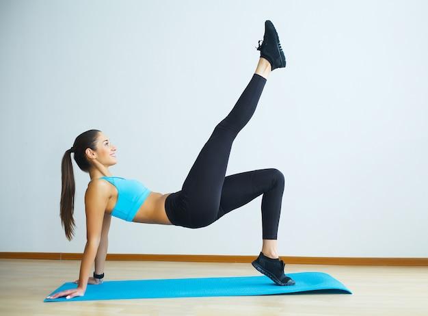 Vrouw in yogaklasse die stijgende hond maken maken.