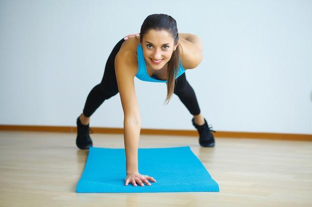 Vrouw in yogaklasse die stijgende onder ogen ziende hond maken