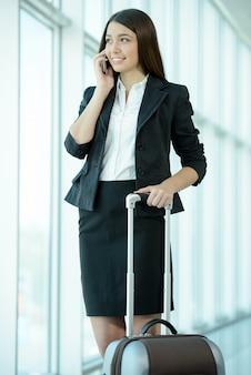Vrouw in zakenreis met zak en mobiel spreken.