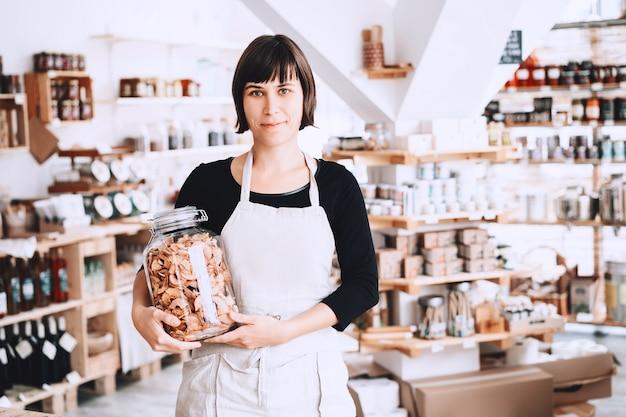 Vrouw in zero waste winkel verkoper assistent in plastic gratis winkel succesvolle eigenaar klein bedrijf