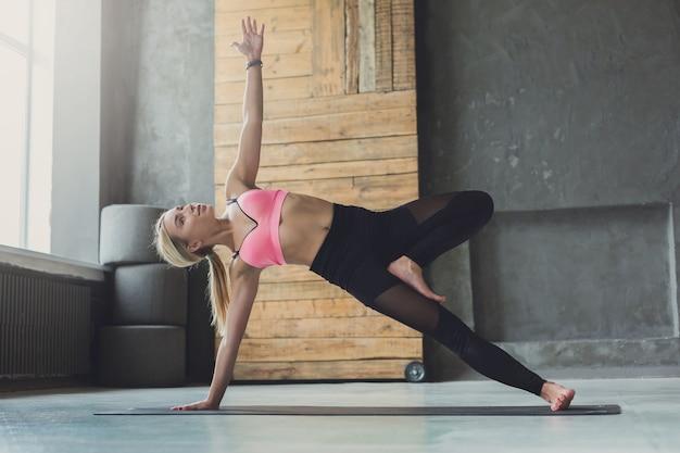 Vrouw in zijplank stelt bij yogales, vasisthasana-oefening. fit yogi meisje balanceren op de mat binnenshuis