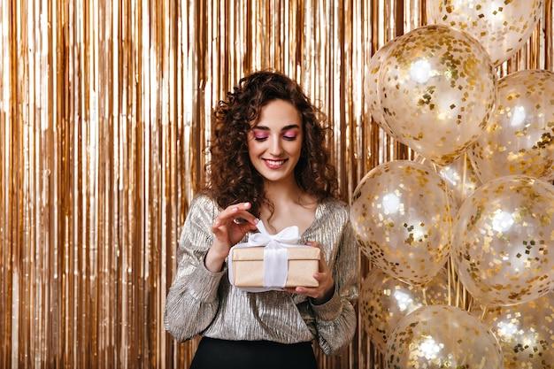 Vrouw in zilveren outfit opent geschenkdoos op achtergrond van ballonnen