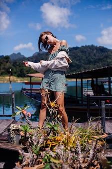 Vrouw in zomerjurk en jas toeristenreizen in thailand, khao sok nationaal park, geweldig uitzicht op boten en meer.