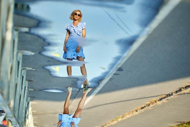 Vrouw in zomerjurk heeft reflectie in plas op straat in de stad