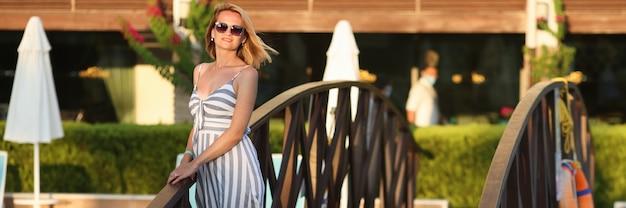 Vrouw in zomerjurk staat naast bruggetje op hotelterrein
