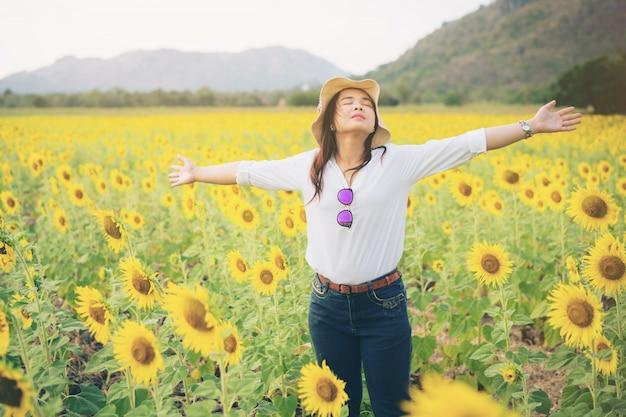 Vrouw in zonnebloem veld. gezond voedingsproduct.