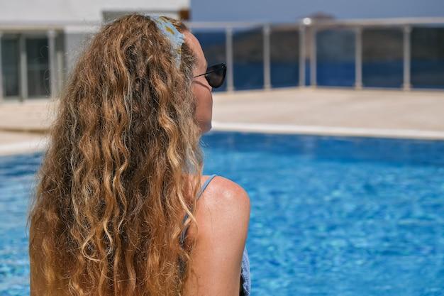 Vrouw in zonnebril en bikini bij het zwembad dat op vakantie zonnebaadt.