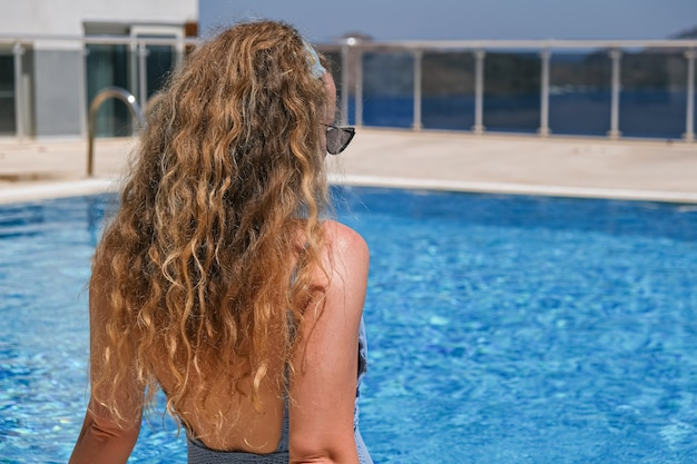 Vrouw in zonnebril en bikini bij het zwembad dat op vakantie zonnebaadt