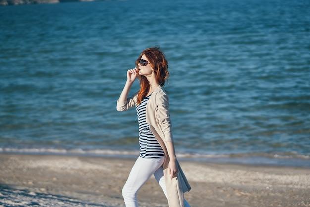 Vrouw in zonnebril en broek wandelen langs het strand in de buurt van de zee in de bergen