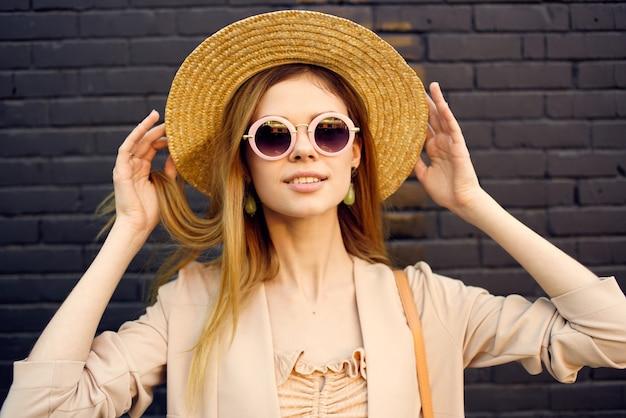 Vrouw in zonnebril en decoratiehoed wandelen buitenshuis bakstenen muur op de achtergrond.