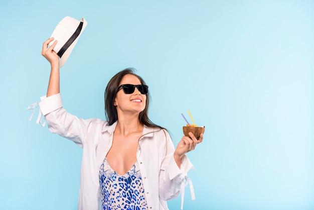 Vrouw in zonnebril met hoed die en gebarsten kokosnoot glimlacht houdt