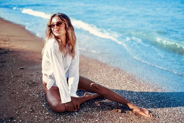 Vrouw in zonnebril met lang haar in zwembroek en wit t-shirt liggend op zomer strand