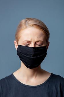 Vrouw in zwart gezichtsmasker met hoofdpijn op grijze ruimte