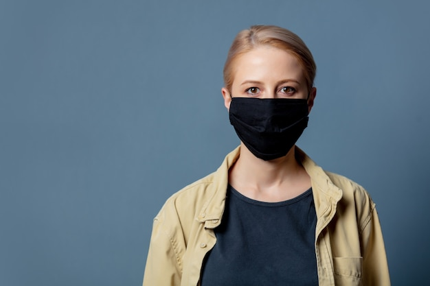Vrouw in zwart gezichtsmasker op grijze ruimte