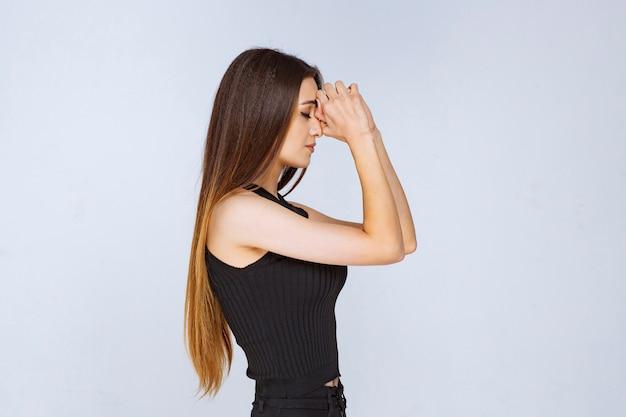 Vrouw in zwart overhemd dat haar handen verenigt en bidt.