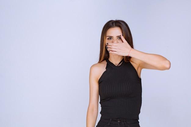 Vrouw in zwart overhemd dat haar neus wegens geur behandelt.