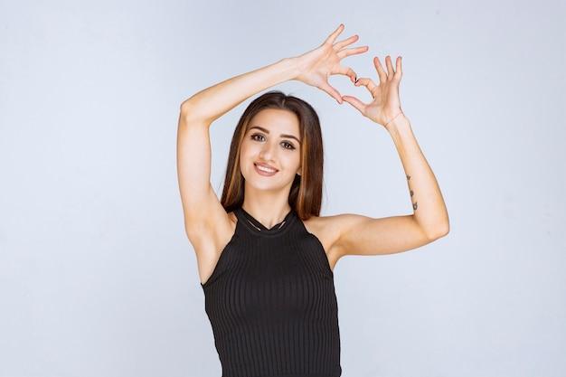 Vrouw in zwart overhemd die het teken van de harthand doen.