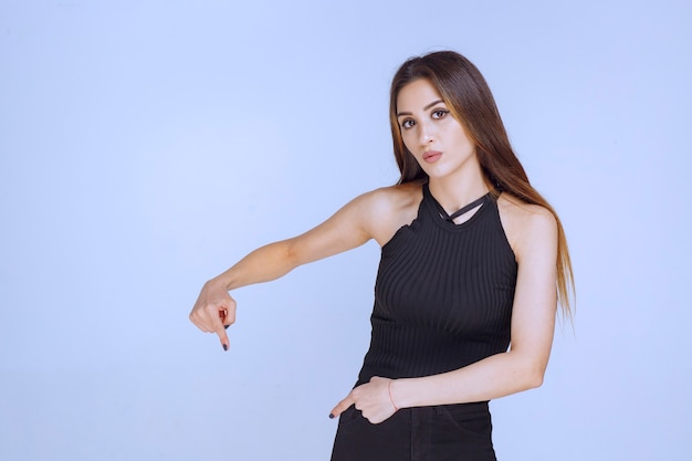 Vrouw in zwart overhemd die naar beneden wijst.