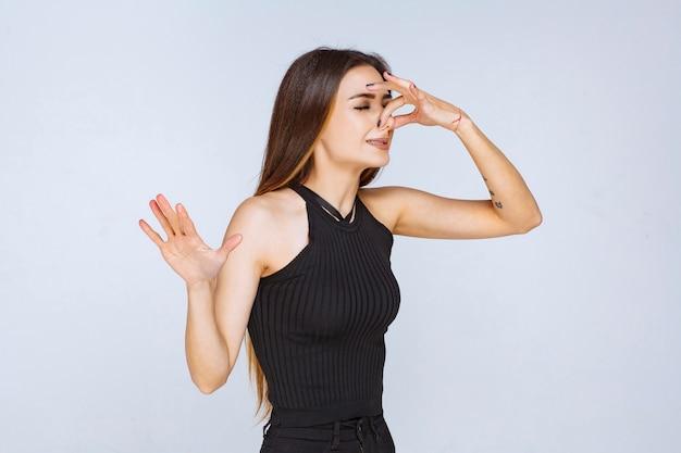 Vrouw in zwart overhemd die slechte geur voelen.