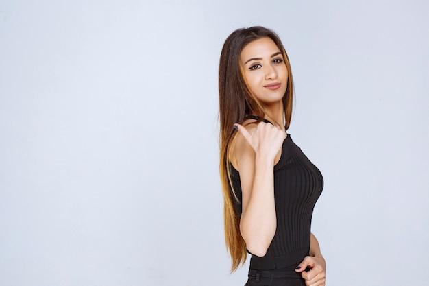 Vrouw in zwart overhemd ergens met vinger wijzen.