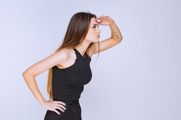 Vrouw in zwart overhemd kijkt uit.