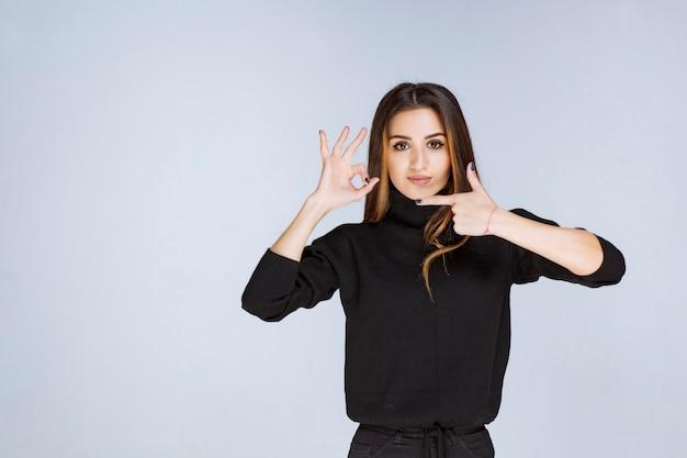 Vrouw in zwart overhemd wijzend op iets aan de linkerkant.