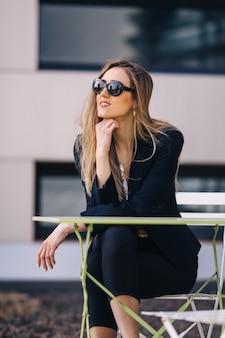 Vrouw in zwart pak en zonnebril zitten aan een tafel in een café