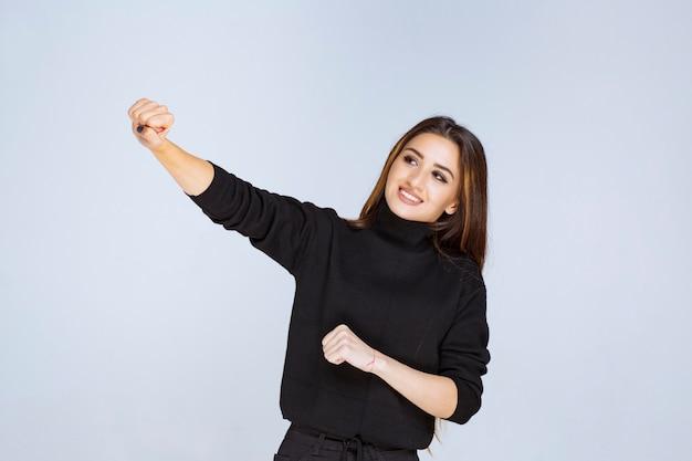 Vrouw in zwart shirt die neutrale en flirterige poses geeft.
