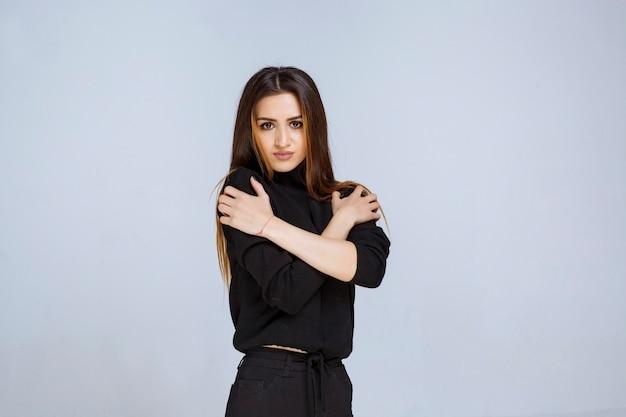 Vrouw in zwart shirt met aantrekkelijke en neutrale poses.