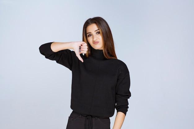 Vrouw in zwart shirt met duim omlaag teken.