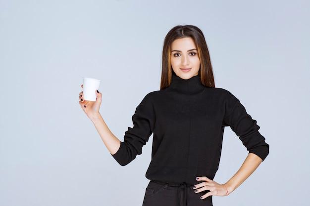 Vrouw in zwart shirt met een wegwerp koffiekopje en het promoten ervan.