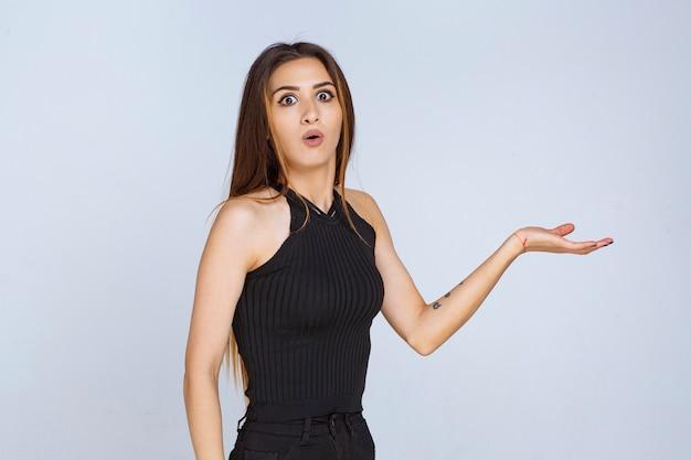 Vrouw in zwart shirt presentatie met open handen maken.