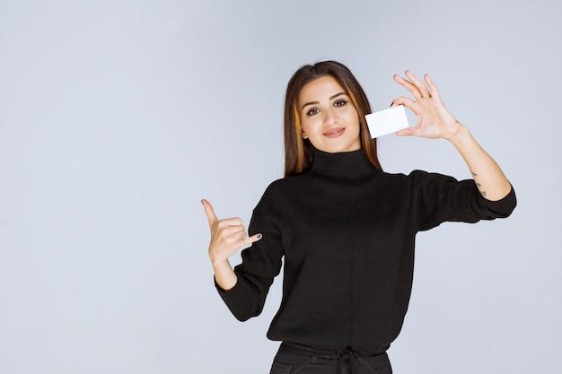Vrouw in zwart shirt toont haar visitekaartje en ziet er tevreden uit.