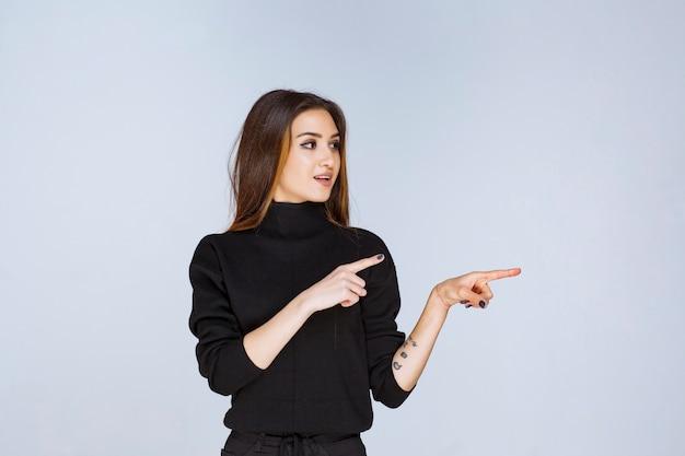 Vrouw in zwart shirt wijst iets aan de rechterkant.