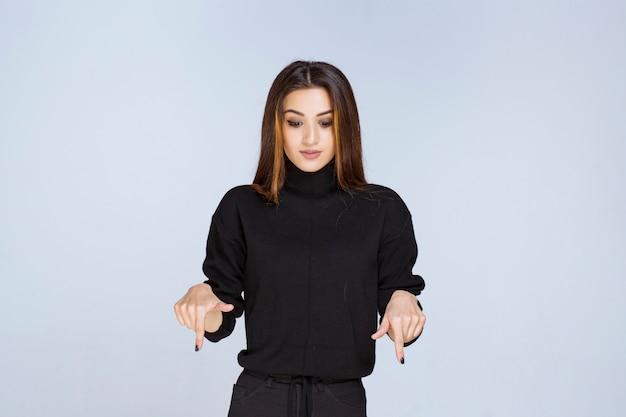 Vrouw in zwart shirt wijzend op keerzijde.