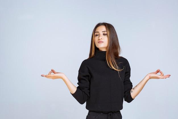 Vrouw in zwart shirt ziet er verward en attent uit.