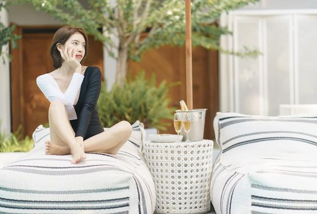 Vrouw in zwart-wit zwembroek ontspannen bij het zwembad en champagne drinken.