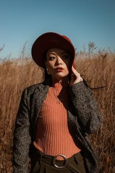 Vrouw in zwart-witte polka dot blazer met lange mouwen en rode hoed op een veld