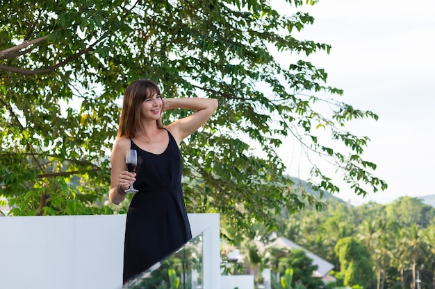 Vrouw in zwarte avondjurk met glas wijn op tropisch balkon