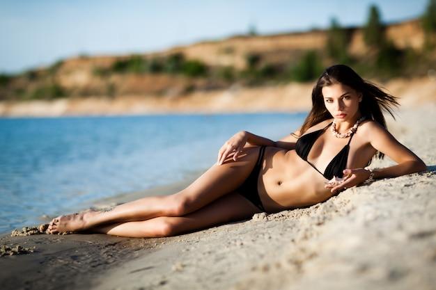 Vrouw in zwarte bikini die op kust ligt