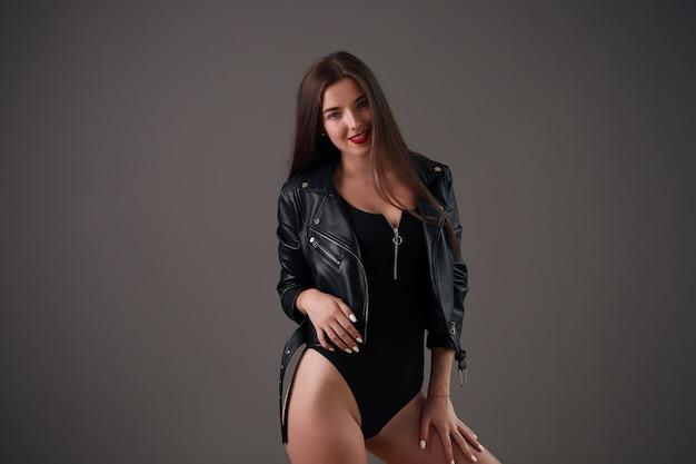Vrouw in zwarte bodysuit. sexy meisjes stijlvolle dame geïsoleerd op grijs. sensuele prachtige jonge vrouw in zwarte bodysuit poseren.