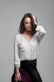 Vrouw in zwarte broek en een wit overhemd. mode portret van een jonge elegante vrouw. mode portret met een jonge blanke model. gekruld haar,